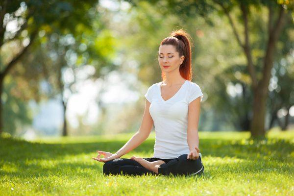 Mujer meditando en el parque